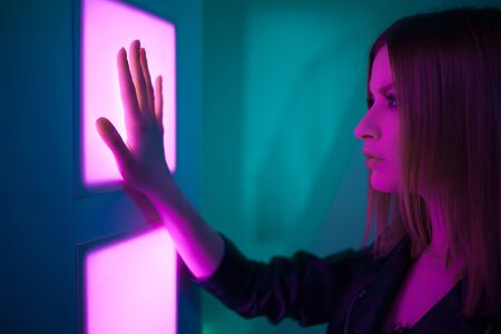 Futuristic style portrait in blue and purple light. Trendy young woman in leather jacket applies palm to enter, Fingerprint identification, concept