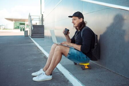 young man with long hair and baseball cap sits on yellow skateboard on the asphalt, leaning his back on gray granite wall, and and drinks coffee, while works on laptop. Copy space