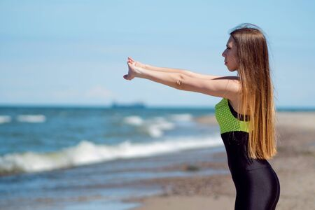 Beautiful female warming up on the beach. Athlete jogging during outdoor workout, facing ocean