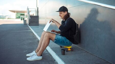 A young man with long hair and a baseball cap sits on a yellow skateboard on the asphalt, leaning his back on a gray granite wall, and works on a laptop 版權商用圖片 - 127798500