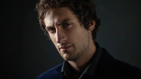 Handsome young brunette man with light eyes in dark clothes on a dark background looks into the distance. Close-up.