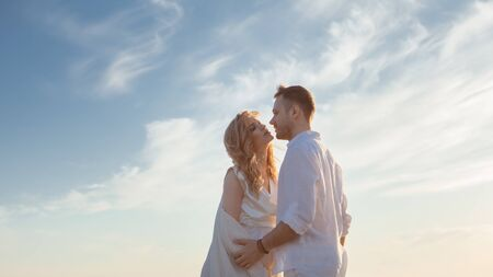 Love, wait for the baby. Portrait of a beautiful couple in white kissing on the background of the sunset sea, sandy beach and sky with clouds. Side view.
