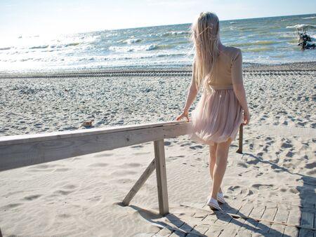 Jeune fille joyeuse au bord de la mer. Jeune femme blonde souriante. Jeune femme sur la plage, liberté et unité avec la nature. Vue arrière Banque d'images