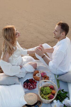 Miłość, czułość. Mężczyzna i kobieta w ciąży urządzili sobie piknik na piasku z poduszkami, latarnią, owocami i słodkimi wypiekami. Karmią się nawzajem i trzymają za ręce. Widok z góry. Zdjęcie Seryjne