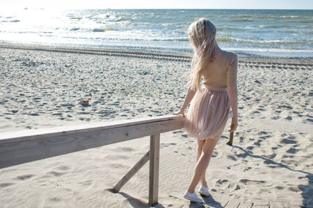 Young cheerful girl on the seashore. Young blonde woman smiling. Young woman on the beach, freedom and unity with nature. Back view