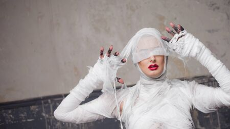 Mummy girl blindfolded. Portrait of a young beautiful woman in bandages all over her body. Halloween or plastic surgery concept
