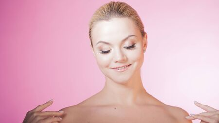 Face care and skin care, health and beauty concept, copy space. Portrait of young beautiful woman, healthy skin and minimum makeup, naturalness and beauty. Charming blonde girl on pink background Stok Fotoğraf