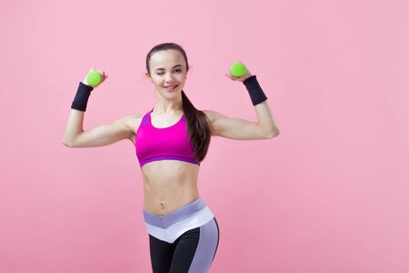 A young athletic attractive brunette girl with a ponytail in a bright top shows off her biceps, holding a green dumbell in her hand on a pink background. Girl power. Copy space Imagens