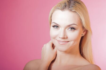 Face care and skin care, health and beauty concept, copy space. Portrait of young beautiful woman, healthy skin and minimum makeup, naturalness and beauty. Charming blonde girl on pink background Banco de Imagens