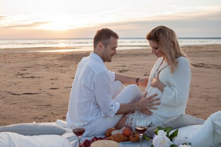 Picnic on the beach. A man and a pregnant woman had a picnic on the sand with a blanket, pillows, a lantern, fruit and sweet pastries. A woman holds a peach in her hand, a man touches her tummy.