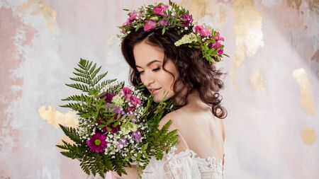 Elegant brunette girl bride with flowers. Beautiful young bride in a lush wedding wreath of fresh flowers. Studio portrait Stockfoto