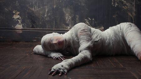 La momia aterradora se arrastra sobre ti. La chica de la venda en el suelo. disfraz de Halloween