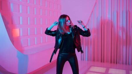 Futuristic style portrait in blue and purple light. Fashion portrait of trendy dancing young woman in leather jacket, Pink color light on a background and her face