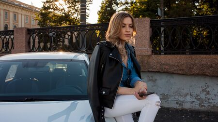 Beautiful and stylish young blonde woman. Portrait with telephone on the background of car. Car sharing car rental service, concept