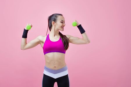 A young athletic attractive brunette girl with a ponytail in a bright top shows off her biceps, holding a green dumbell in her hand on a pink background. Girl power. Copy space Фото со стока