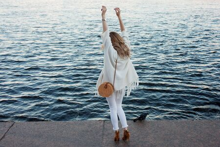 Portrait of smiling woman in a white cardigan. Laughing girl on the background of street, freedom and happiness on the background of water, walk on the seafront or river Фото со стока