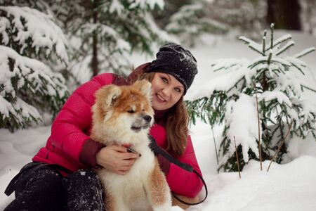 Portrait with a cute fluffy puppy. Winter walk with a dog. young woman walks with the puppy, snowy winter Фото со стока