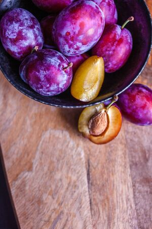 Delicious juicy blue plums in a bowl on the table, textured wooden table, natural materials and natural eco-friendly products, healthy food, fruit Фото со стока