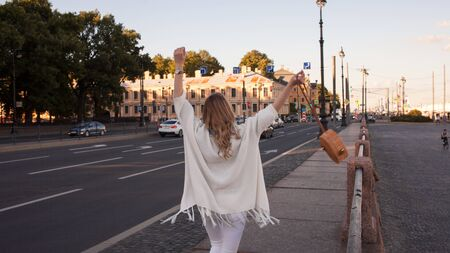 Portrait of smiling woman in a white cardigan. Laughing girl on the background of street, freedom and happiness