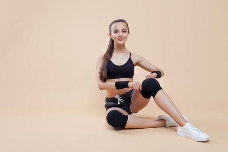 A young brunette girl with wireless headphones in shorts and top with a calm smile is preparing for a workout, tying up her knee pads and bandages on her hands. Copy space Фото со стока