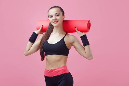 A brunette girl, attractive, is standing, holding a yoga mat ver the shoulders. Copy space Фото со стока