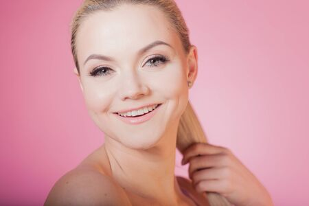 Face care and skin care, health and beauty concept, copy space. Happy young woman smiling, healthy skin and minimum makeup, naturalness and beauty. Charming blonde girl on pink background