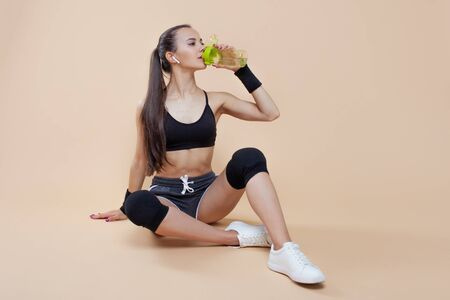 A cute athletic brunette girl, in a tight-fitting sports uniform, sits, rests after a workout, in black kneecaps, with a bottle for sports nutrition in her hand, drinking water . Copy space