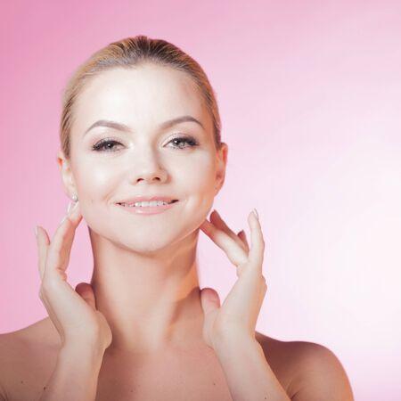 Gezichtsverzorging en huidverzorging, gezondheids- en schoonheidsconcept, kopieer ruimte. Gelukkige jonge vrouw die lacht, gezonde huid en minimale make-up, natuurlijkheid en schoonheid. Charmant blond meisje op roze achtergrond