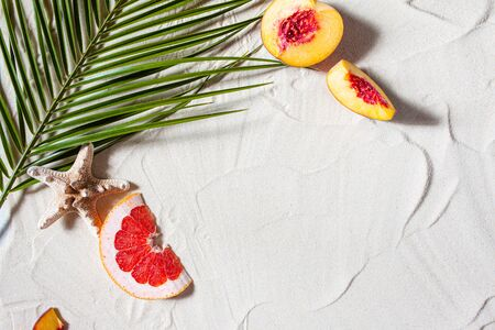 Beach vacation. A palm leaf and juicy fruits lie on white fine sand. Close-up, top view, desktop wallpaper. Copyspace. Фото со стока