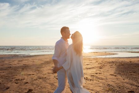 Love, sunset, romance. A young couple in long white soft clothes walking, resting, hugging against the backdrop of a calm sea landscape, sunset.