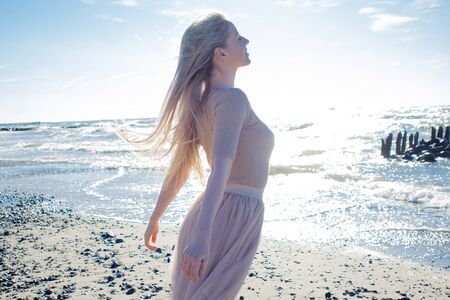 Young cheerful girl on the seashore. Young blonde woman smiling. Young woman on the beach, freedom and unity with nature