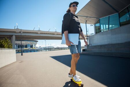 A man with long brunette hair with a laptop in his hand is riding a skateboard in frame. Dynamic photo. 版權商用圖片 - 129212876