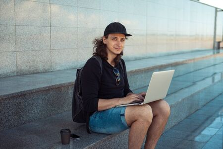 A young brunette man with long hair is sitting on the granite steps with a laptop spread out on his lap and looking thoughtfully into the distance. Summer windy day. Copy space. Side view