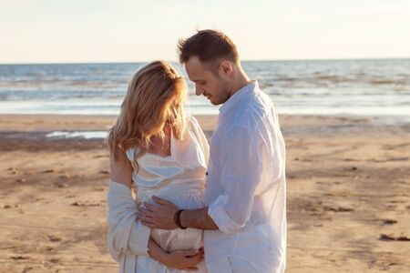Love, waiting for the baby. A young beautiful couple, pregnant woman and a man, in white loose flying clothes, walk along the sand along the coastline, hold hands, against the backdrop of the sunset. Stok Fotoğraf