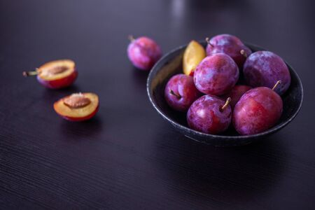 Fresh delicious plums in a plate on a black background. Summer fruits at home