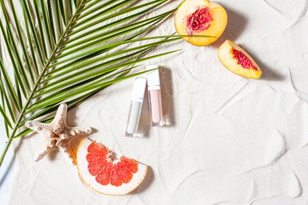 Vacation. Lip gloss in a transparent tube lies on the sand, surrounded by vibrant fruits, corals, and palm leaves. Close-up, top view, desktop wallpaper. Copyspace.