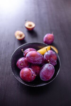 Delicious juicy blue plums in a bowl on the table, dark background.