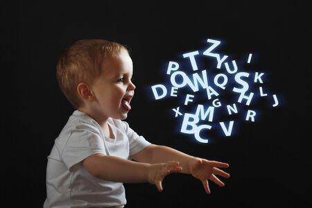 Baby sagt, das Konzept der Probleme mit Legasthenie und Dysgraphie. Ein Kind lernt sprechen, ein Junge auf schwarzem Grund, rechts eine Wolke chaotischer Buchstaben