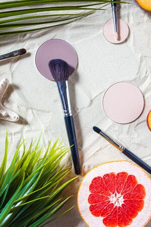 Dry cosmetic decorative product in a round refile lies on the sand, surrounded by bright fruits, corals, and palm leaves. Powder, highlighter, bronzer, blush with a brush. Close-up, top view
