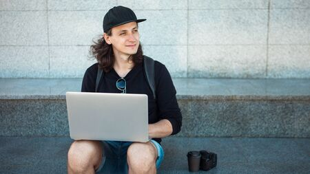 Freelancer working in the open air, concept, young man with long hair sits on the granite steps in the shade, with a laptop. Summer windy day. Copy space. Front view 版權商用圖片 - 129309495