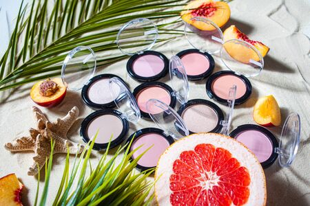Charming beach. A lot of blush, bronzers, highlighter in round stylish packaging surrounded by bright fruits, corals, and palm leaves lie on the white sand. Close-up, top view