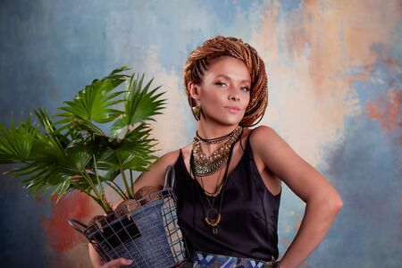 Southern flavor. A young tanned woman with afro braids smiles holding a big pot with a tropical plant. On her neck she has large jewels in ethnic style. Фото со стока - 129309945
