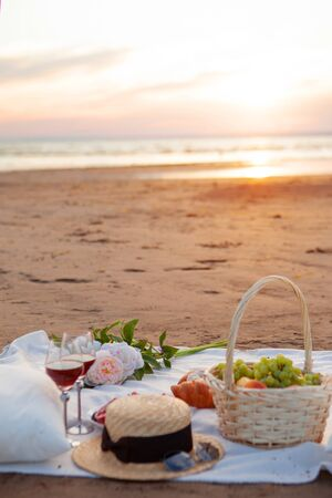Picnic in the rays of the setting sun on the sand. On the plaid lies a basket of fruit, glasses, flowers and sweet pastries. Nearby is a straw hat.