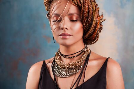 Southern spices. portrait of a gorgeous smiling young woman, with beautiful stylish, fashionable, summer make up, and large gold and silver ornaments. Hair tucked into the hair from afro braid. Фото со стока