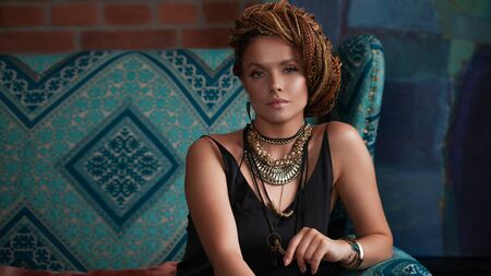 Southern spices. Luxurious young woman with afro-hairs, an intricate hairstyle, blue eyes, highlighter, with large jewels in ethnic style in loft-style interiors, on a turquoise sofa. Фото со стока