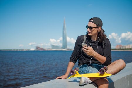 A young man sitting on the embankment with a yellow skateboard on his lap makes a photo of the cityscape against the sky, clouds, sea, and modern urban architecture. Copy space 版權商用圖片 - 129310023