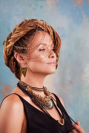 Southern flavor. Portrait of a luxurious tanned woman, pensive, stylish, with an exotic hairstyle and large jewels, necklace, earrings, against the background of a multi-colored textured wall.