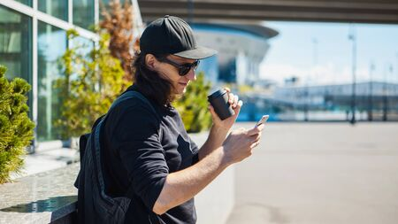 A man in black glasses, a black baseball cap and shoots coffee on the street on a smartphone. Side view. Paparazzi. Private investigations.
