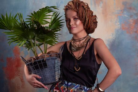 Southern flavor. A young tanned woman with afro braids smiles holding a big pot with a tropical plant. On her neck she has large jewels in ethnic style. Фото со стока - 129310252