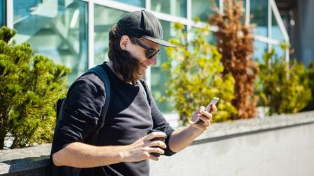 A man in black glasses, a black baseball cap and shoots coffee on the street on a smartphone. Side view. Paparazzi. Private investigations. 版權商用圖片 - 129310254